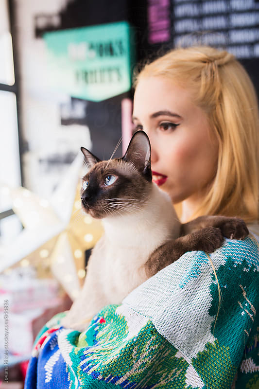 Portrait of a young woman and her siamese cat by Jovana Rikalo for Stocksy United