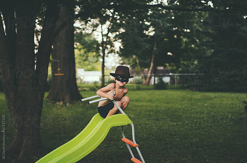 A boy sitting on a green slide. by Ali Deck for Stocksy United