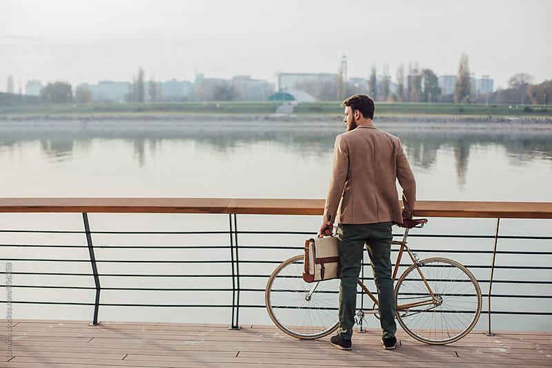 Man With a Bike Standing by the River by Lumina for Stocksy United