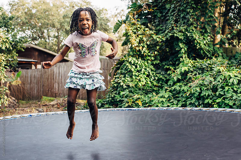 Happy black girl on trampoline by Gabriel (Gabi) Bucataru for Stocksy United