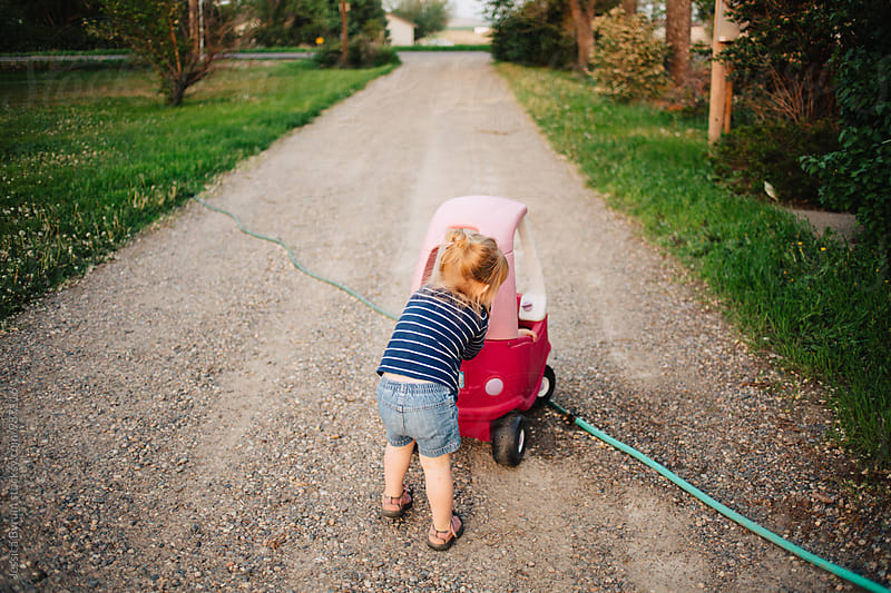 Toddler girl pushing her brother down the driveway in a pink toy car. by Jessica Byrum for Stocksy United