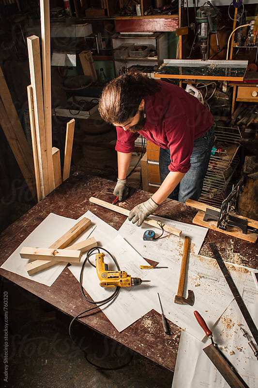 Carpenter working with wood in his workshop/look from above. by Audrey Shtecinjo for Stocksy United