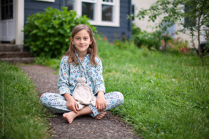 Brunette girl in pajamas sits on the walkway in front of her house by Carleton Photography for Stocksy United