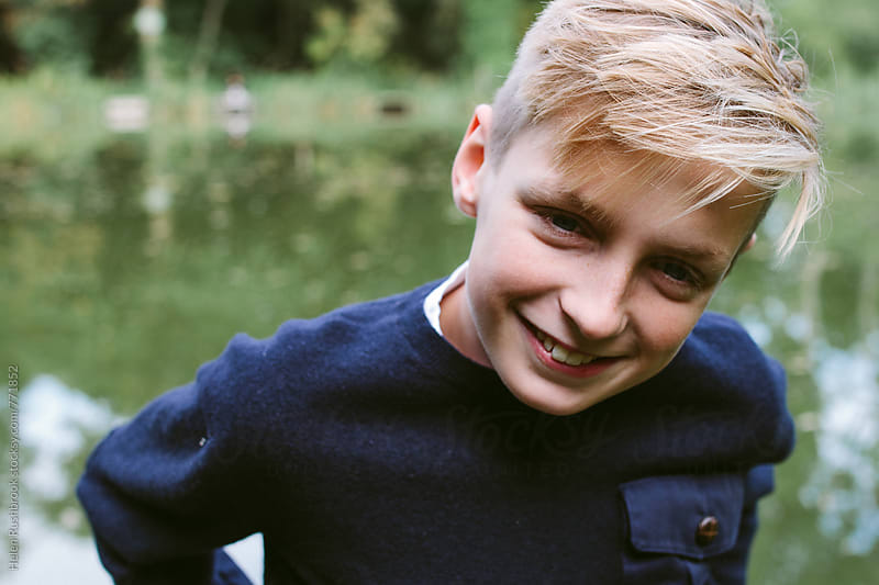 Portrait of a teenage boy outdoors in autumn by Helen Rushbrook for Stocksy United