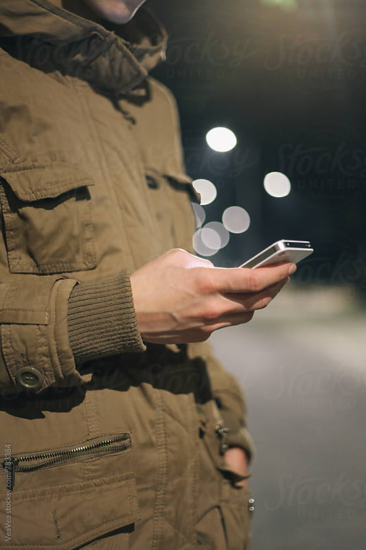 Woman browsing on her phone in the street during the night. Just hands and body. by VeaVea for Stocksy United