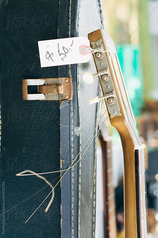 Vintage guitar for sale in flea market by Kristin Duvall for Stocksy United