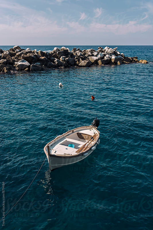 Motor boat in Italian beautiful blue rocky bay by Trent Lanz for Stocksy United
