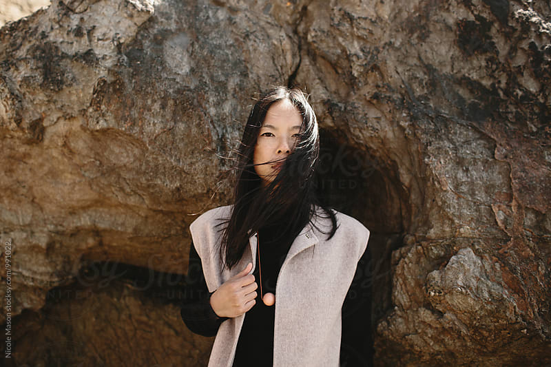portrait of beautiful stylish asian woman on rocky coast by Nicole Mason for Stocksy United