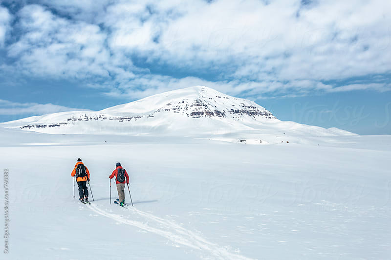 Two skiers touring in the mountains of Iceland by Søren Egeberg Photography for Stocksy United