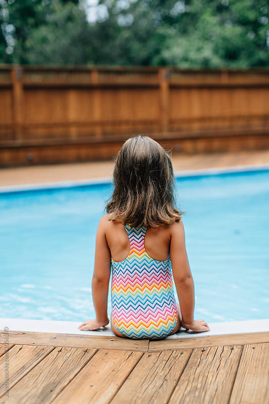 Cute young girl in a swimsuit sitting by a pool by Jakob for Stocksy United
