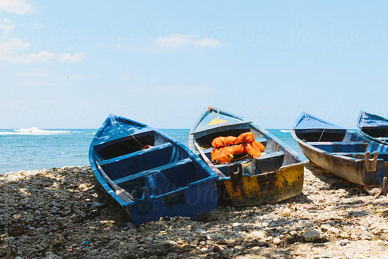 Four rustic fishing boats on shoreline by Trent Lanz for Stocksy United
