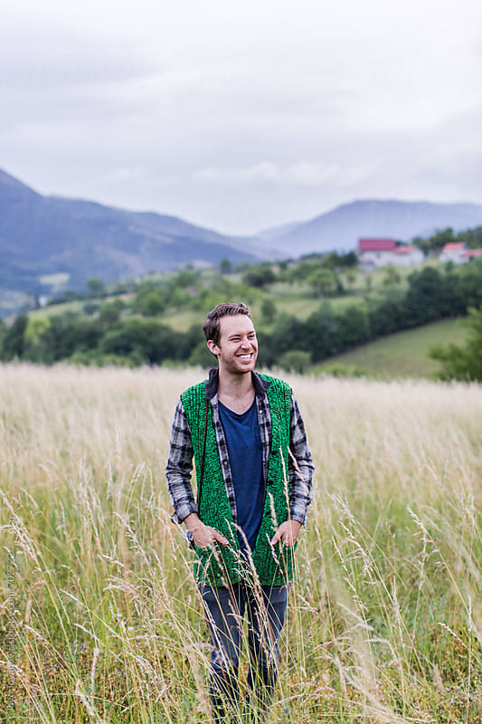 Young man standing in a field smiling by Jovo Jovanovic for Stocksy United