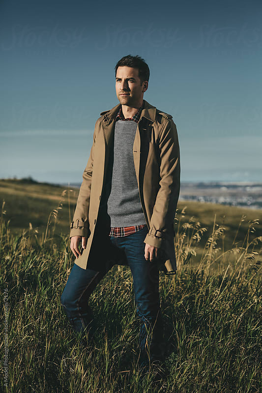 Man on a hill in a trenchcoat by Ania Boniecka for Stocksy United