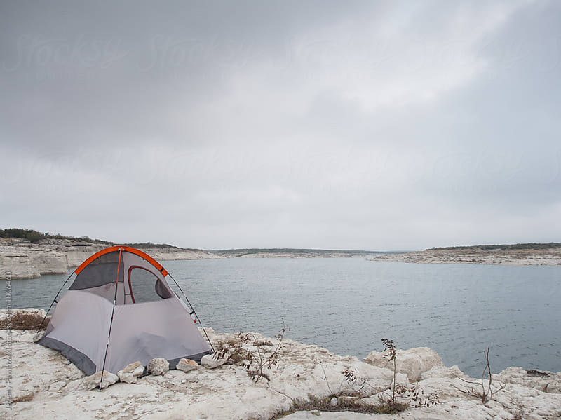 Lone tent set up on cliff overlooking water by Jeremy Pawlowski for Stocksy United