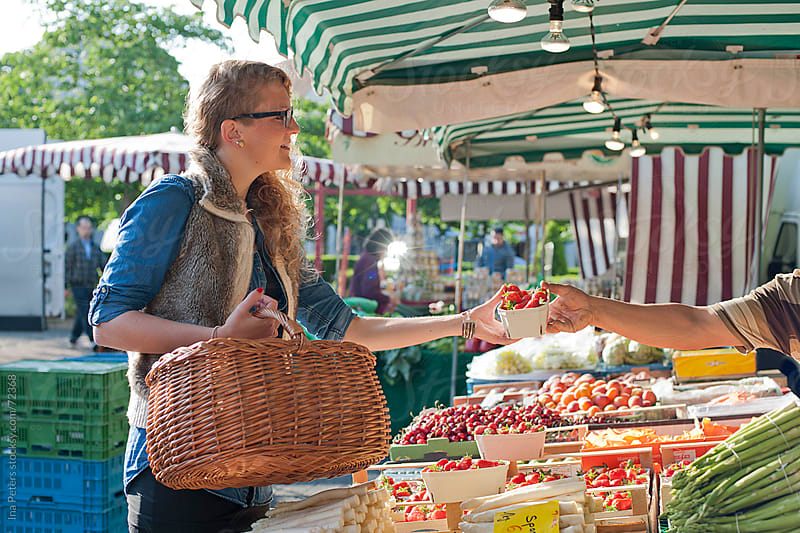 Girl buying some strawberries on a farmer's market by Ina Peters for Stocksy United
