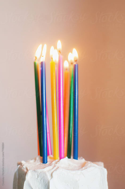 A birthday cake with candles by Chelsea Victoria for Stocksy United
