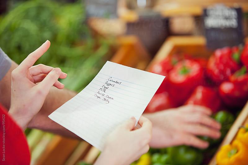 Market: Woman Holding Grocery List by Sean Locke for Stocksy United