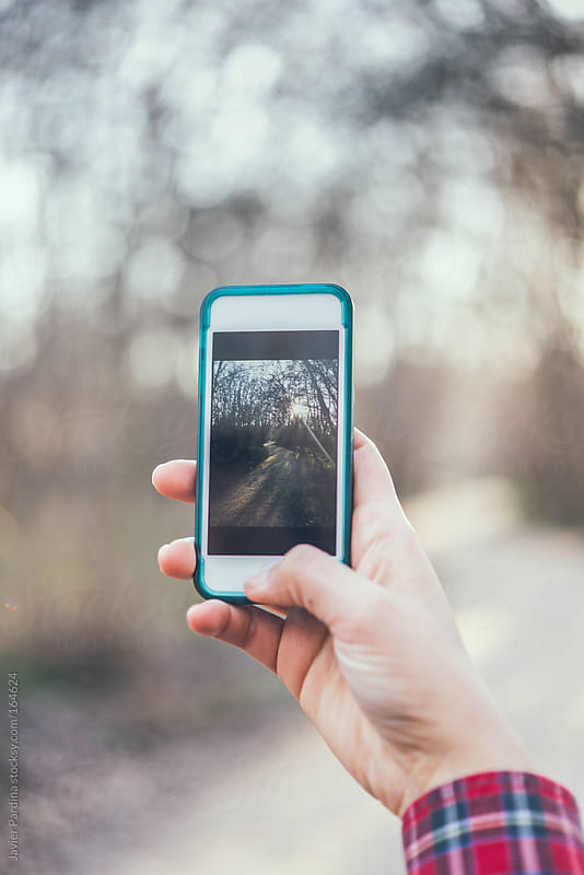 girl taking photo with mobile device by Javier Pardina for Stocksy United
