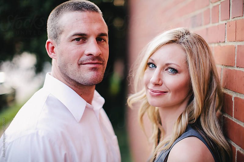 A beautiful couple in love standing by a brick wall by Jakob for Stocksy United
