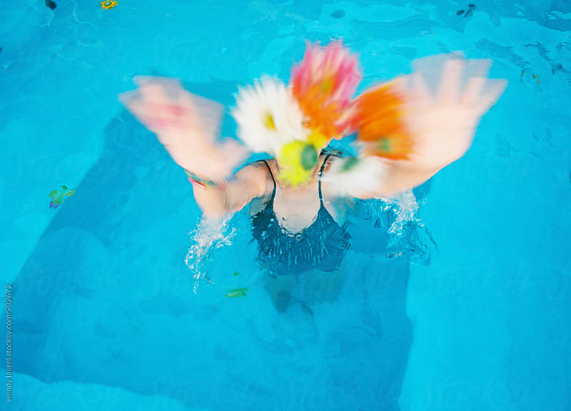 girl throwing colored flowers up in blue swimming pool by wendy laurel for Stocksy United