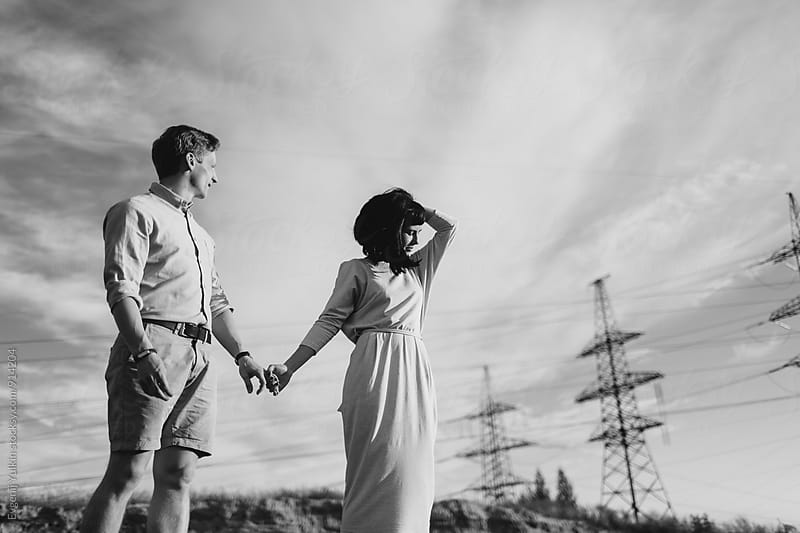 Young couple standing beside the power tower by Evgenij Yulkin for Stocksy United