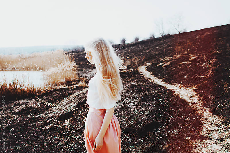 Young blonde woman walks on a black field by Sergey Filimonov for Stocksy United
