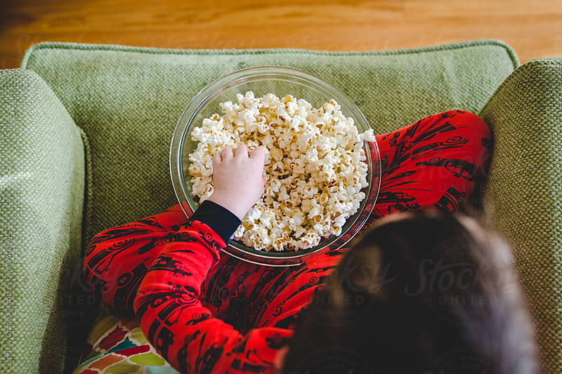 Young child sitting with a bowl of popcorn by Lindsay Crandall for Stocksy United