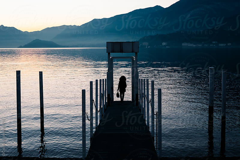 Silhouette of a woman on the jetty at lake by GIC for Stocksy United