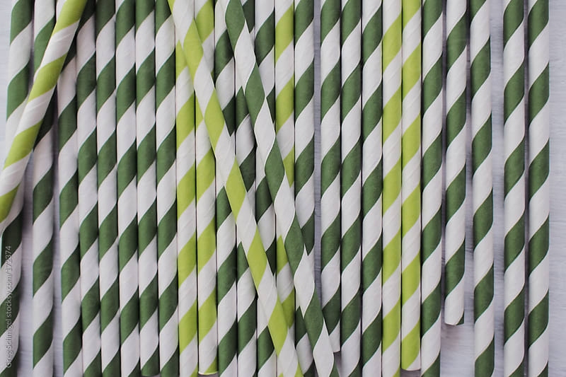 A group of striped green paper straws on a white kitchen table. by Greg Schmigel for Stocksy United