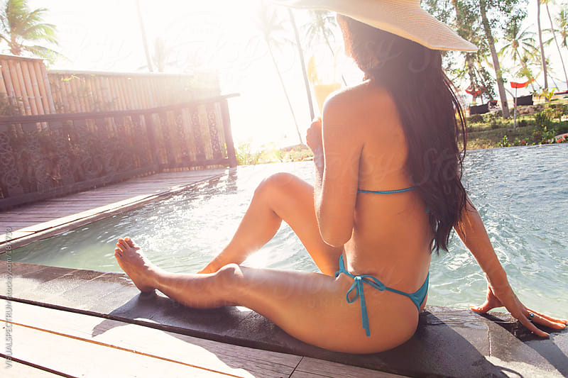 Pretty Woman Sunbathing By Private Pool by VISUALSPECTRUM for Stocksy United