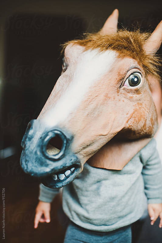 Toddler wearing horse mask by Lauren Naefe for Stocksy United