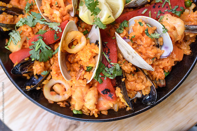 paella with clams, mussels, calamari, and shrimp by Deirdre Malfatto for Stocksy United