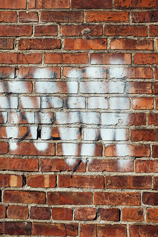 Spray paint covering graffiti on old brick wall by Paul Edmondson for Stocksy United