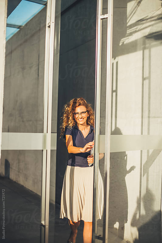 Caucasian businesswoman leaving office building.. by Studio Firma for Stocksy United