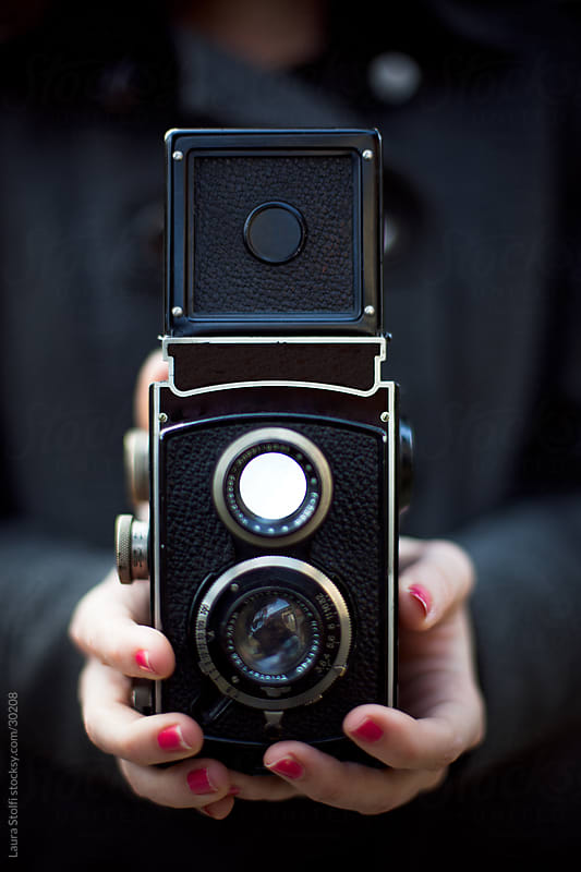 Young woman holding in her hands an ancient medium-format twin lens reflex camera by Laura Stolfi for Stocksy United
