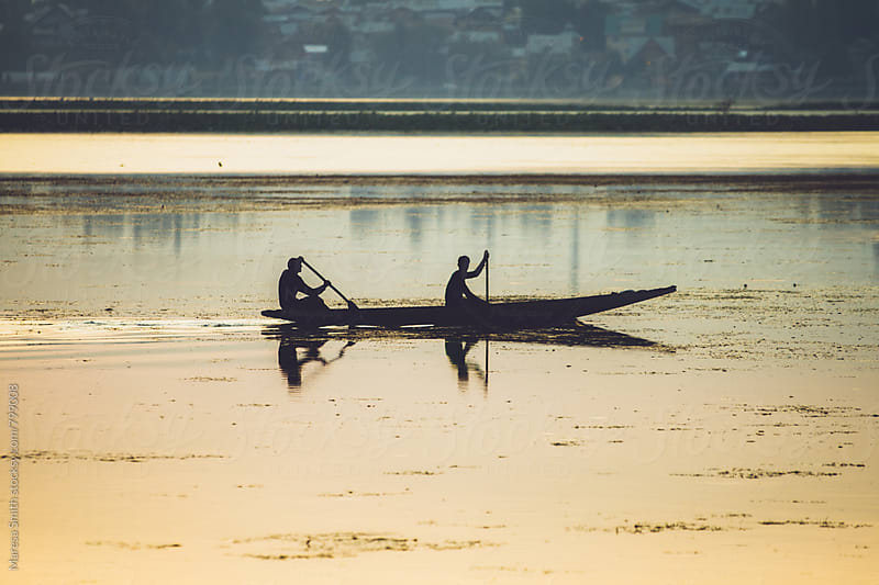Silhouettes on a paddle boat in India at dusk by Maresa Smith for Stocksy United