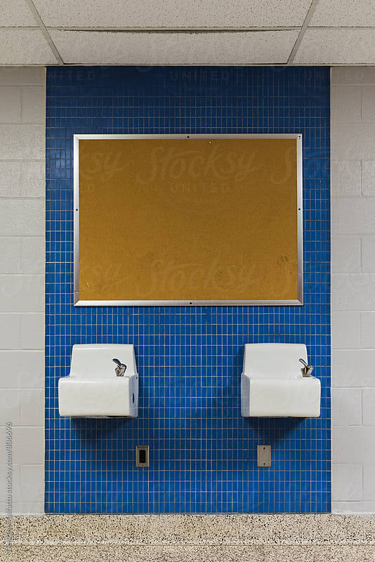 two drinking fountains and a bulletin board on blue tile by Deirdre Malfatto for Stocksy United