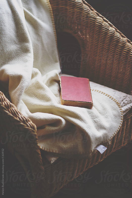 An old book, a blanket and a wicker chair. by Helen Rushbrook for Stocksy United