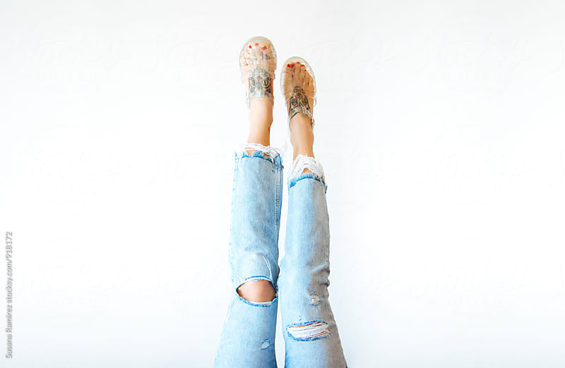 Female Legs with ripped jeans and sandals by Susana Ramírez for Stocksy United