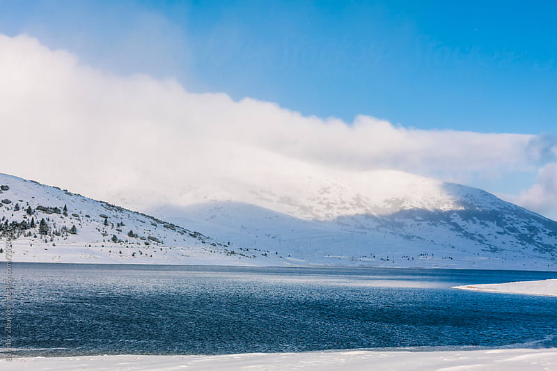 Lake During The Winter With Snowy Mountains Background by Borislav Zhuykov for Stocksy United