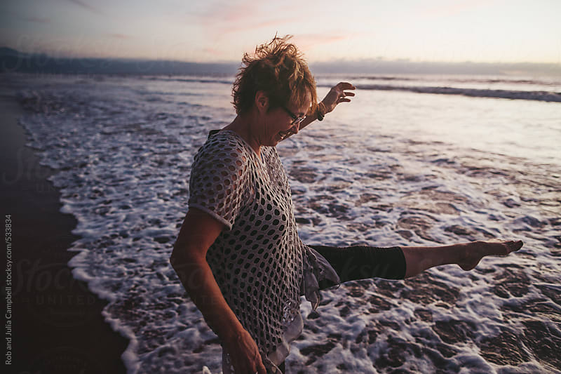Energetic middle aged woman dancing outside on ocean beach at sunset by Rob and Julia Campbell for Stocksy United