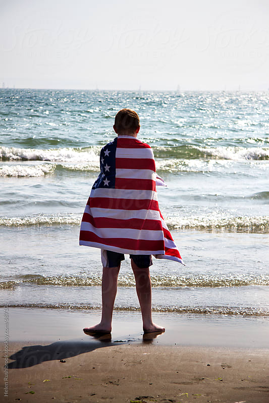 A teenage boy wrapped in a USA flag towel, standing looking out to sea. by Helen Rushbrook for Stocksy United