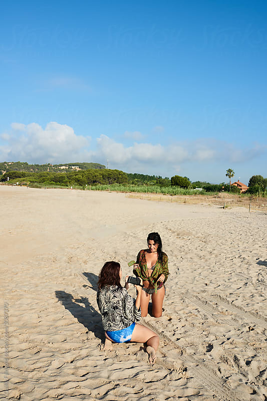 Girlfriends making photos on beach by Guille Faingold for Stocksy United
