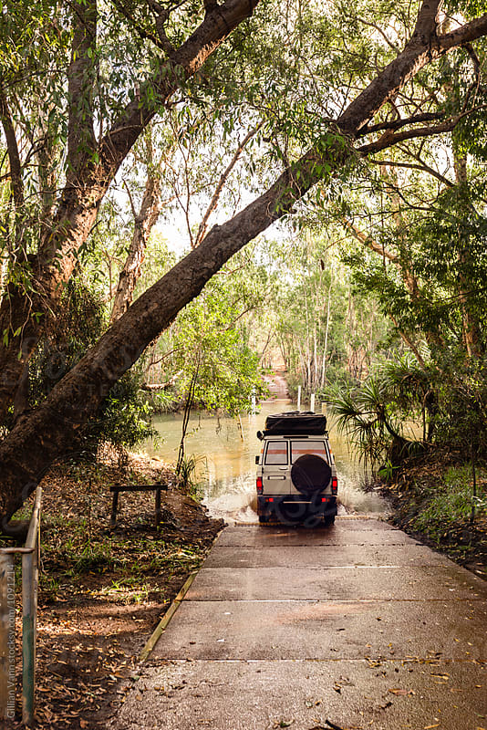 a large four wheel drive makes a splash as it enters a creek, NT, Australia by Gillian Vann for Stocksy United