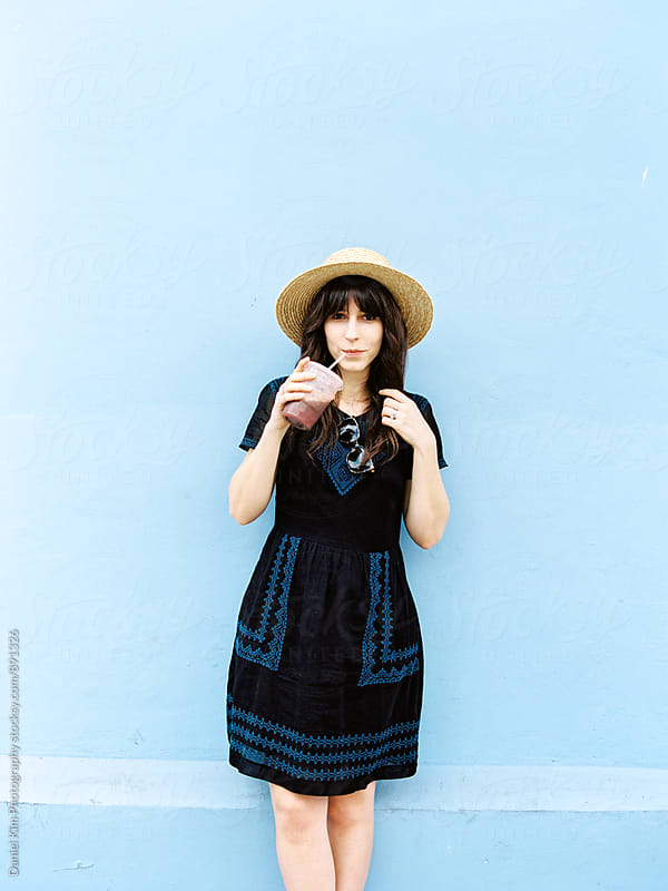 Woman in front of blue wall by Daniel Kim Photography for Stocksy United