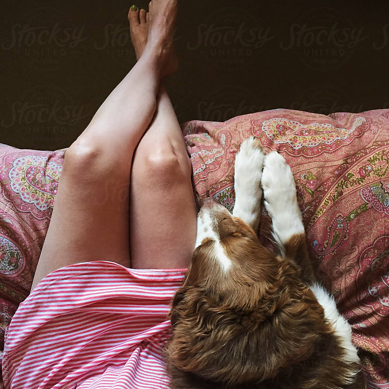 Woman and dog resting on bed by Holly Clark for Stocksy United