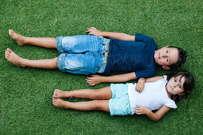 Brother and Sister Lying on the Grass by VICTOR TORRES for Stocksy United