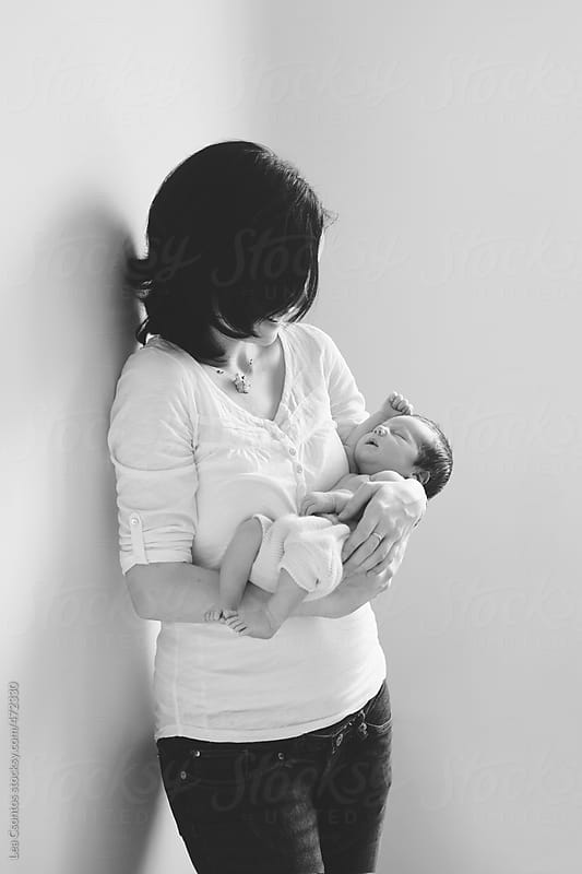Mother holding her newborn baby in her arms by Lea Csontos for Stocksy United