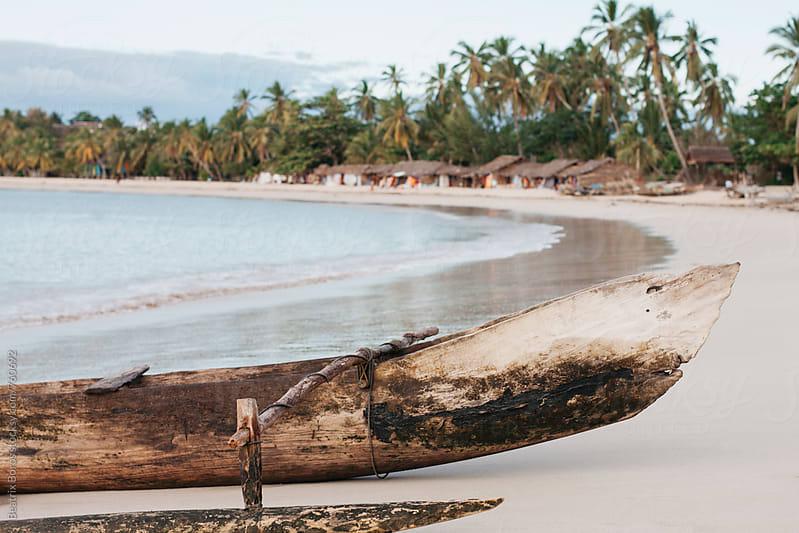 A malgache wooden pirogue on a sandy beach by Beatrix Boros for Stocksy United