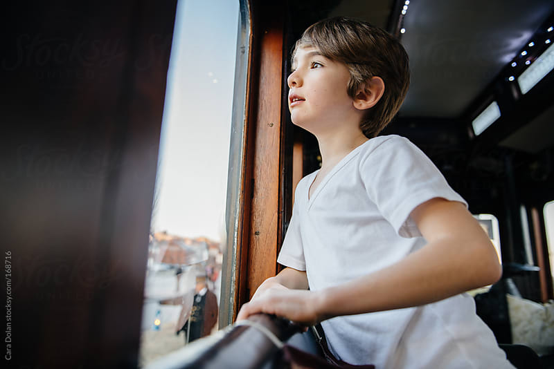 Boy looks out the window while riding on a train by Cara Dolan for Stocksy United